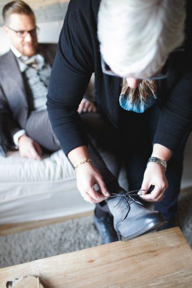 Trouwfotograaf voorbereidingen bruiloft bruidegom trekt zijn schoenen aan