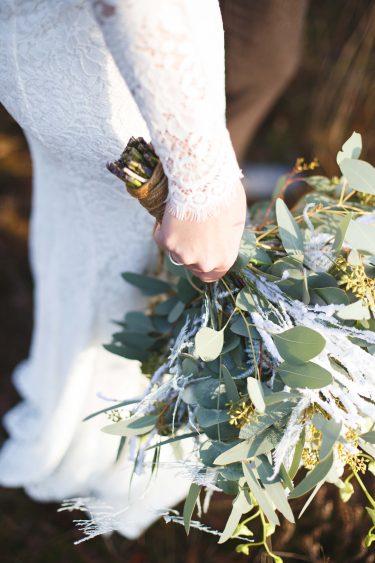 Trouwfotograaf bruid houdt boeket met eucalyptus en gipskruid vast