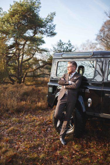 Trouwfotograaf bruidegom leunt tegen trouwauto in bosrijke omgeving