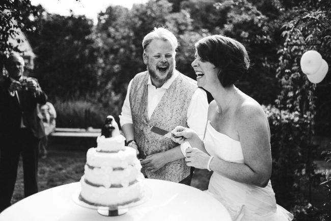 Bruidsfotograaf Apeldoorn bruiloft thuis in tuin bruidstaart aansnijden in Enschede
