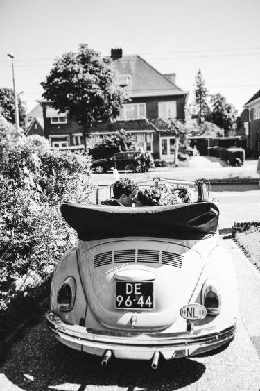 Trouwfotograaf trouwauto op oprit van huis met een kussend bruidspaar