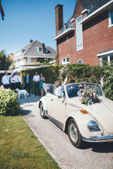 Trouwfotograaf trouwauto op oprit bruidspaar zwaait familie uit
