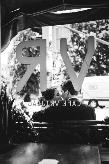 Trouwfotograaf bruidspaar zit voor Café Vrijdag waar hun eerste date plaatsvond