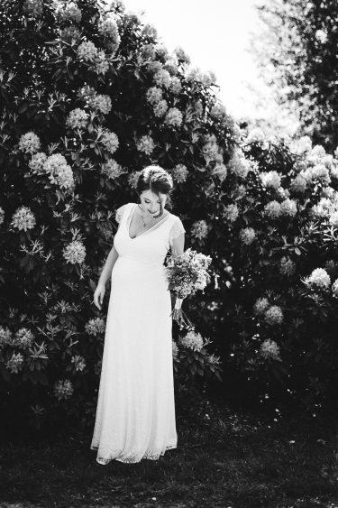 Trouwfotograaf bruid staat voor bloemenzee met bruidsboeket in handen