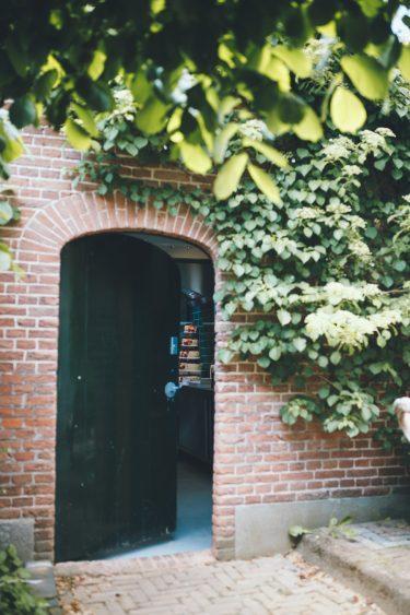 Trouwfotograaf witte bruidstaart met bloemen staat verstopt in keuken