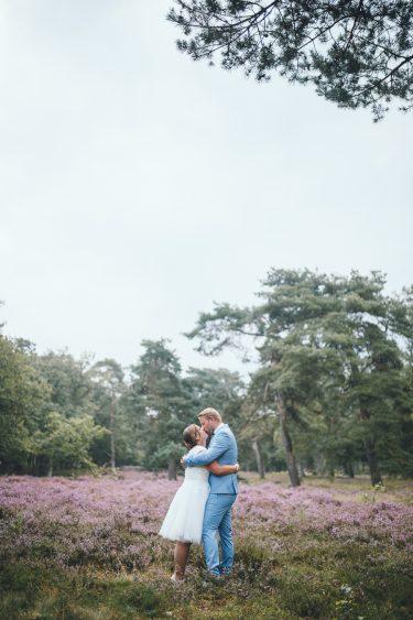 Trouwfotograaf bruidspaar staat midden in de bloeiende heide in september in Hilversum