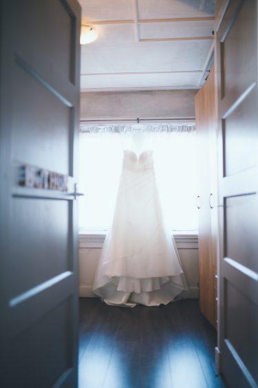 Trouwfotograaf trouwjurk hangend voor het raam in meisjeskamer