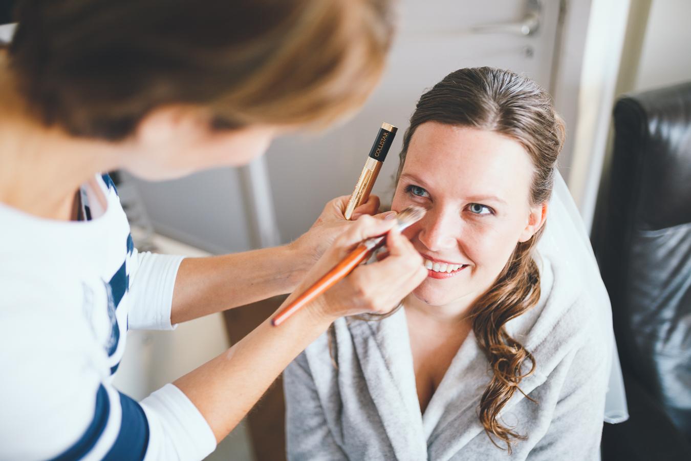 Trouwfotograaf bruid in visagie met make-up in badjas voorbereidingen