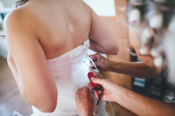 Trouwfotograaf trouwjurk aantrekken met zaklamp