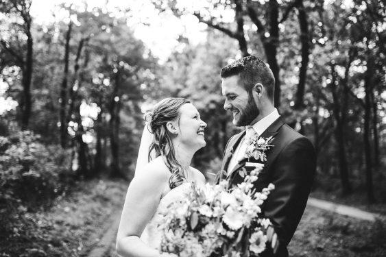 Trouwfotograaf bruidspaar kijkt elkaar aan bij trouwfoto's in bos met boeket