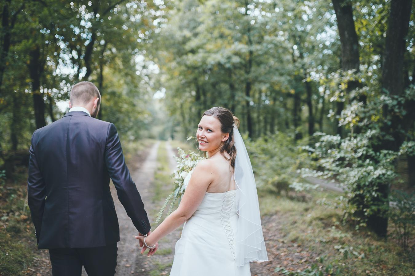 Trouwfotograaf bruidspaar trouwfoto's in bos hand in hand bruid kijkt over haar schouder