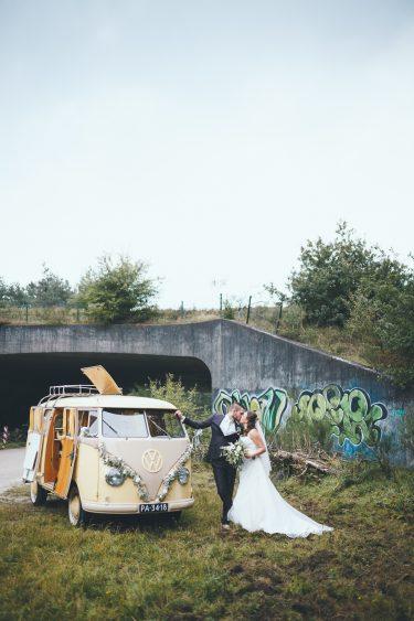Trouwfotograaf bruidspaar maakt trouwfoto's met geel Volkswagenbusje en viaduct met graffiti