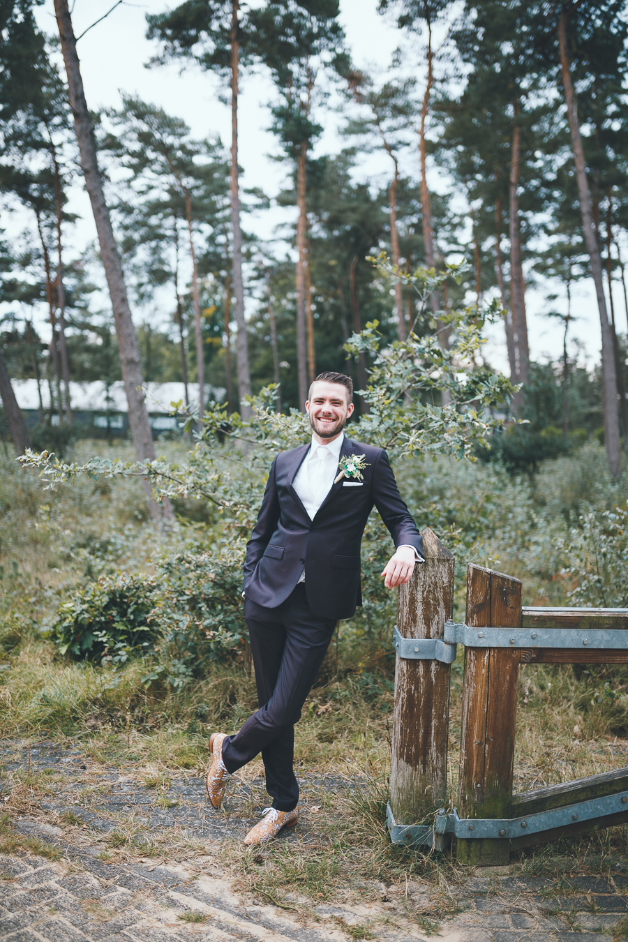 Trouwfotograaf bruidegom in bruin pak in groene omgeving Radio Kootwijk