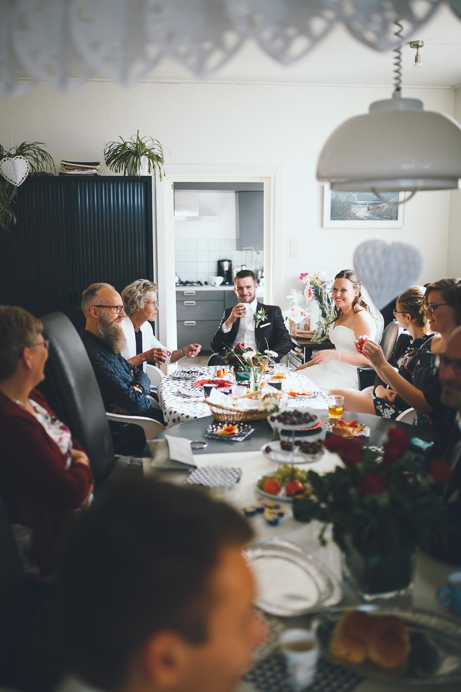Trouwfotograaf bruidspaar luncht aan tafel met familie