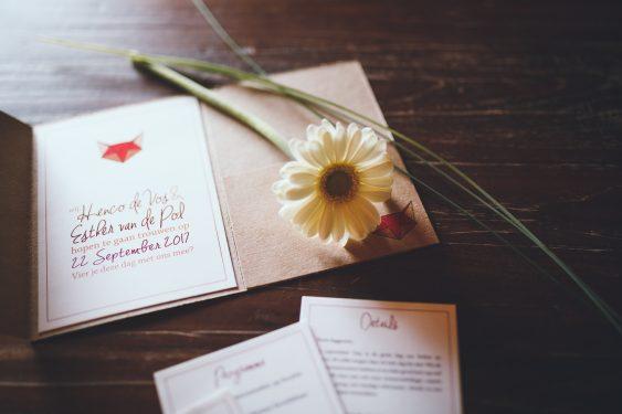Trouwfotograaf uitnodiging bruiloft met kraft en bloem