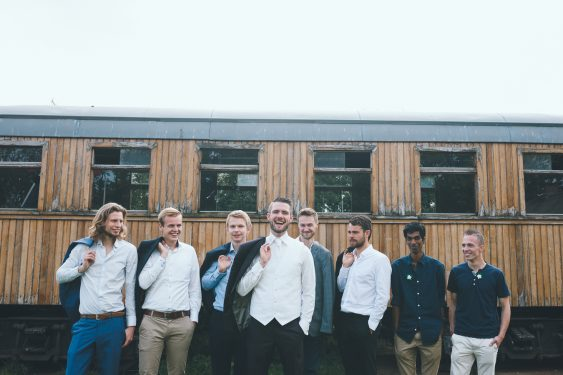 Trouwfotograaf groepsfoto vriendengroep van bruidegom met jasjes over schouder