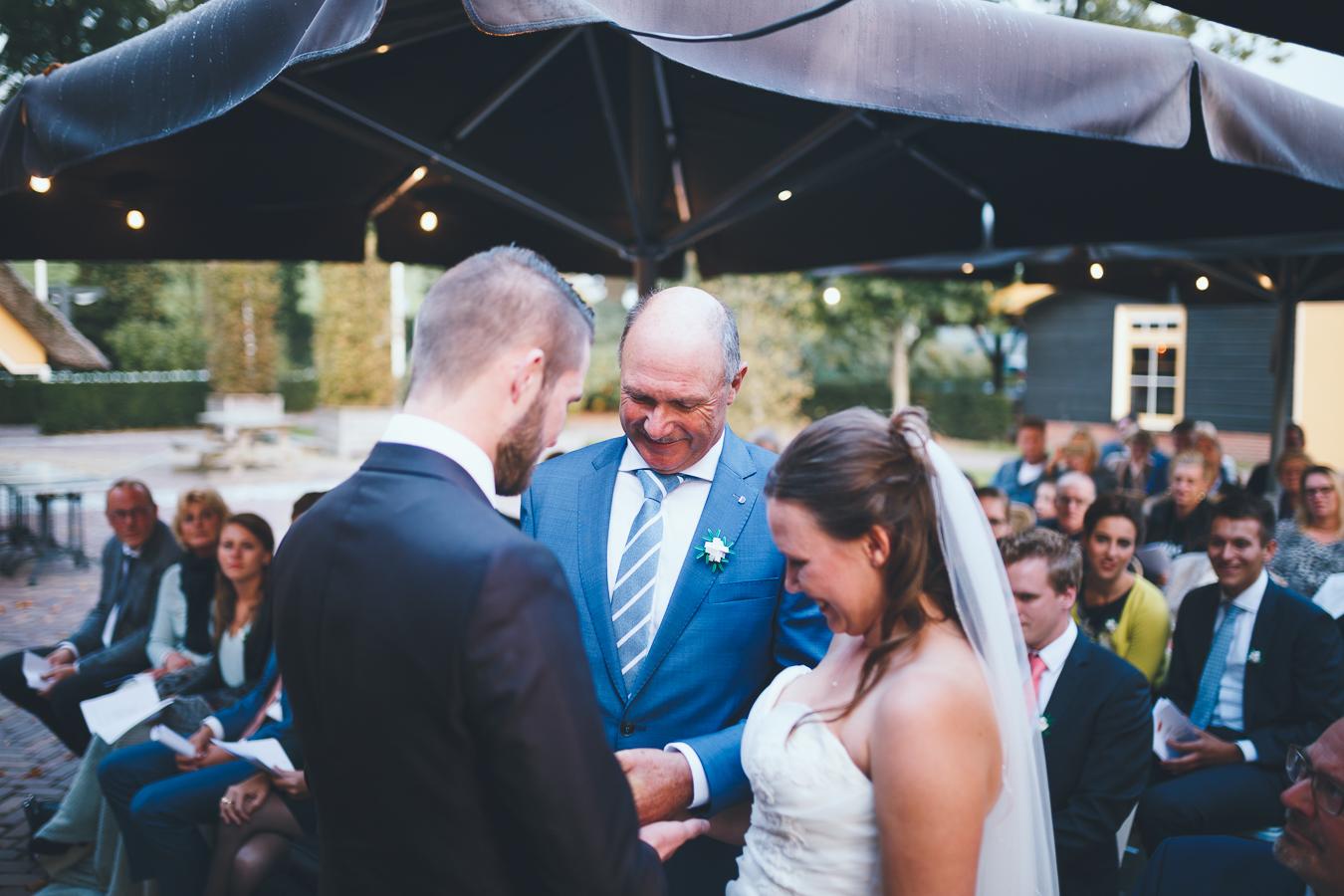 Trouwfotograaf bruid wordt door haar vader aan bruidegom gegeven
