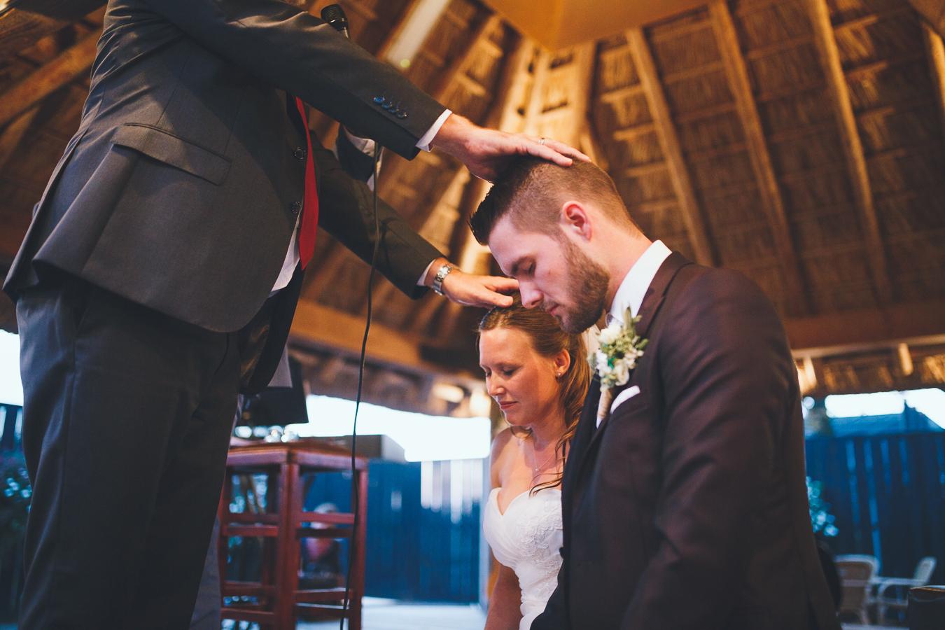 Trouwfotograaf bruidspaar wordt gezegend tijdens kerkelijke ceremonie