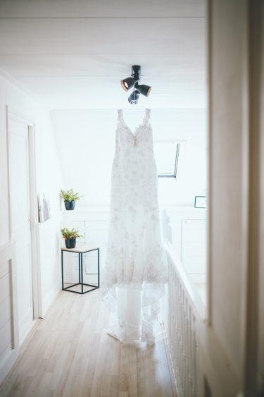 Trouwjurk met sleep hangt op lichte overloop tijdens bruiloft thuis op erf van oude boerderij trouwfotograaf Apeldoorn