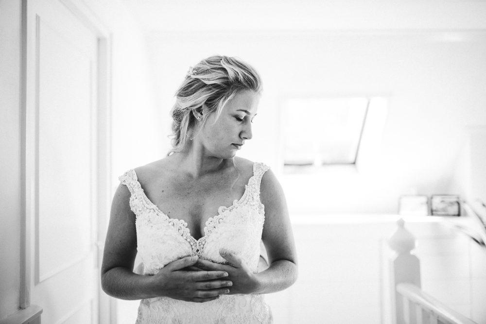 Bruid trekt haar jurk aan op lichte overloop tijdens bruiloft thuis op erf van oude boerderij trouwfotograaf Apeldoorn