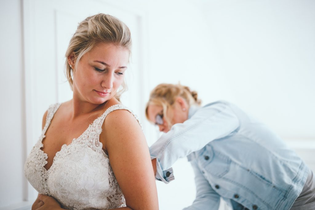 Bruid trekt trouwjurk aan en moeder helpt tijdens bruiloft thuis op erf van oude boerderij trouwfotograaf Apeldoorn