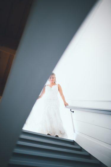 Bruid loopt naar beneden in trouwjurk tijdens bruiloft thuis op erf van oude boerderij trouwfotograaf Apeldoorn