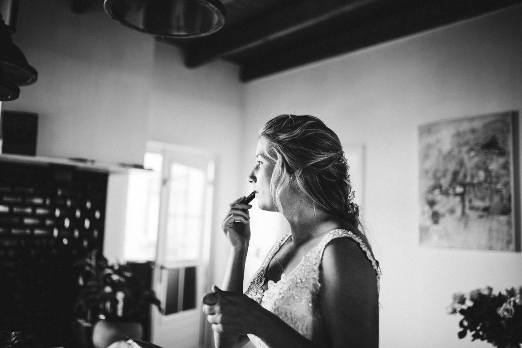Bruid doet lippenstift op tijdens voorbereidingen voor de bruiloft thuis op erf van oude boerderij trouwfotograaf Apeldoorn