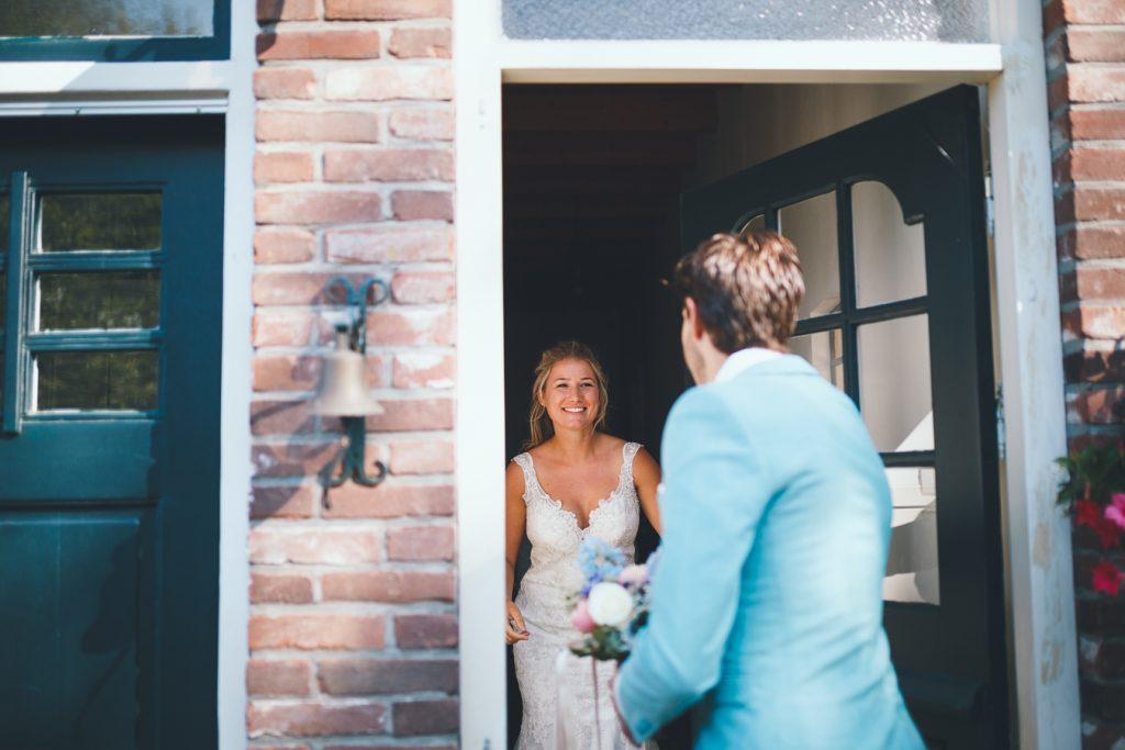 Bruid doet de deur open wanneer bruidegom aanbelt om elkaar voor het eerst te zien tijdens bruiloft thuis op erf van oude boerderij trouwfotograaf Apeldoorn