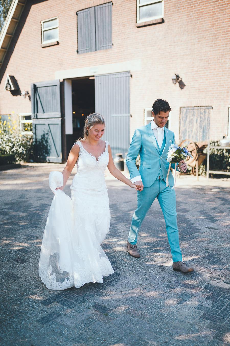 Bruid en bruidegom wandelen hand in hand over het erf tijdens bruiloft thuis op erf van oude boerderij trouwfotograaf Apeldoorn
