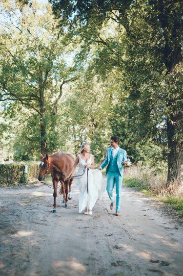 Bruid en bruidegom lopen met paard over zandweg tijdens bruiloft thuis op erf van oude boerderij trouwfotograaf Apeldoorn