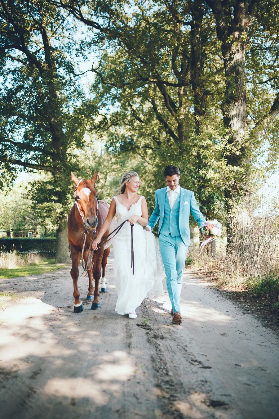 Bruid en bruidegom lopen met een paard naast zich op een zandweg tijdens bruiloft thuis op erf van oude boerderij trouwfotograaf Apeldoorn