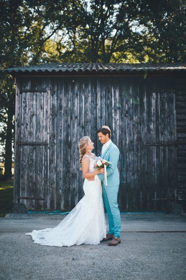 Bruid en bruidegom staan tegenover elkaar voor een oude grijze schuur tijdens bruiloft thuis op erf van oude boerderij trouwfotograaf Apeldoorn