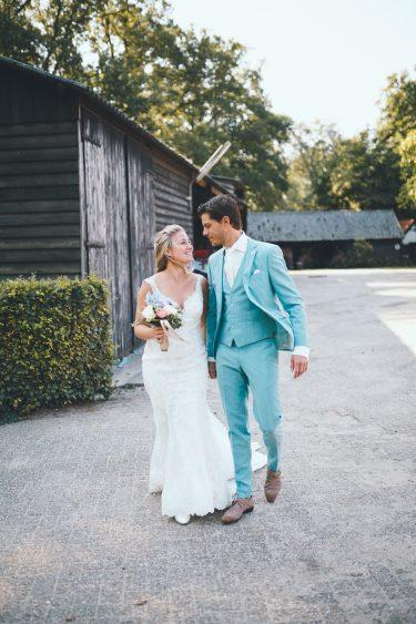 Bruid en bruidegom lopen hand in hand over erf en kijken elkaar lief aan tijdens bruiloft thuis op erf van oude boerderij trouwfotograaf Apeldoorn