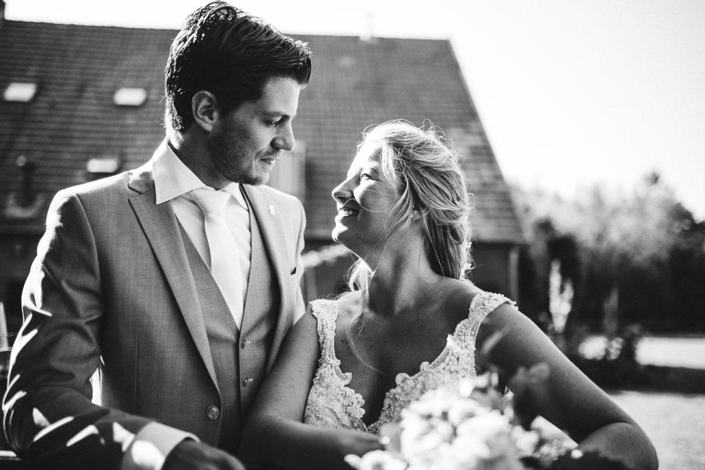 Bruid en bruidegom staan achter hun huis bij een hek en kijken elkaar lief aan tijdens bruiloft thuis op erf van oude boerderij trouwfotograaf Apeldoorn