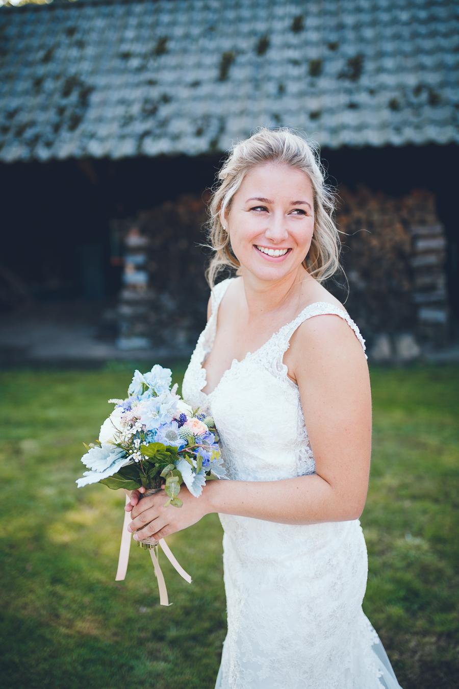 Bruid met boeket in haar handen kijkt over haar schouder weg tijdens bruiloft thuis op erf van oude boerderij trouwfotograaf Apeldoorn