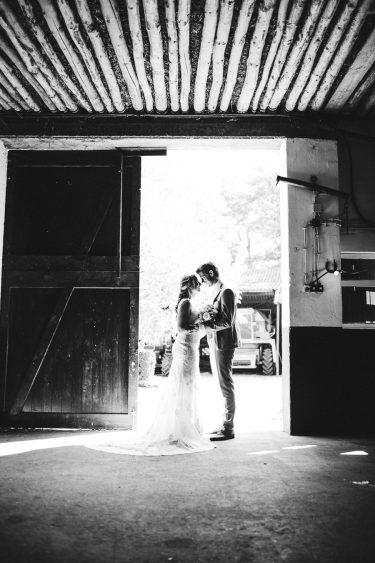 Bruid en bruidegom staan tegenover elkaar in de opening van een oude schuur en raken elkaar aan met hun neus aan tijdens bruiloft thuis op erf van oude boerderij trouwfotograaf Apeldoorn