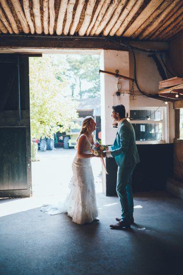 Bruid en bruidegom staan in een oude schuur en lachen naar elkaar tijdens bruiloft thuis op erf van oude boerderij trouwfotograaf Apeldoorn