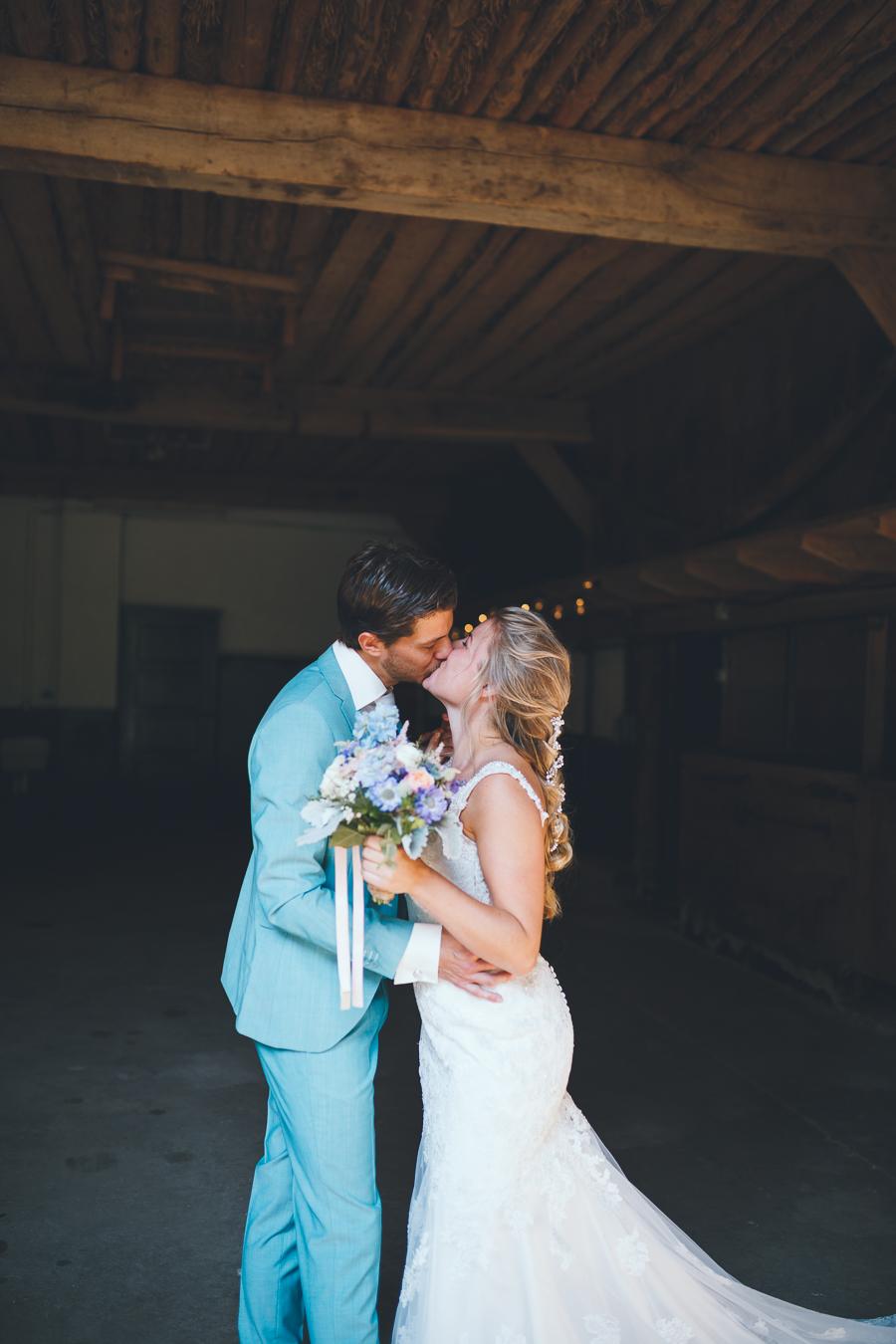 Bruid en bruidegom staan in een oude schuur en zoenen elkaar met lichtjes in de achtergrond tijdens bruiloft thuis op erf van oude boerderij trouwfotograaf Apeldoorn