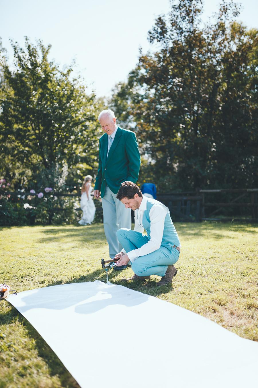 Bruidegom slaat spijker in de witte loper en trouwambtenaar in groene colbert kijkt toe tijdens bruiloft thuis op erf van oude boerderij trouwfotograaf Apeldoorn
