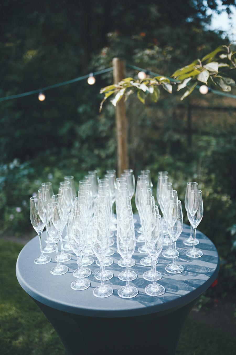 Lege glazen champagne staan klaar op statafel in achtertuin tijdens bruiloft thuis op erf van oude boerderij trouwfotograaf Apeldoorn