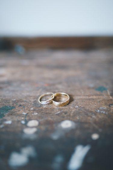 Trouwringen op oude werkbank tijdens bruiloft thuis op erf van oude boerderij trouwfotograaf Apeldoorn