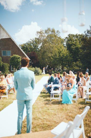 Bruid komt met vader aangelopen bruidegom staat al klaar bij het altaar tijdens bruiloft thuis op erf van oude boerderij trouwfotograaf Apeldoorn