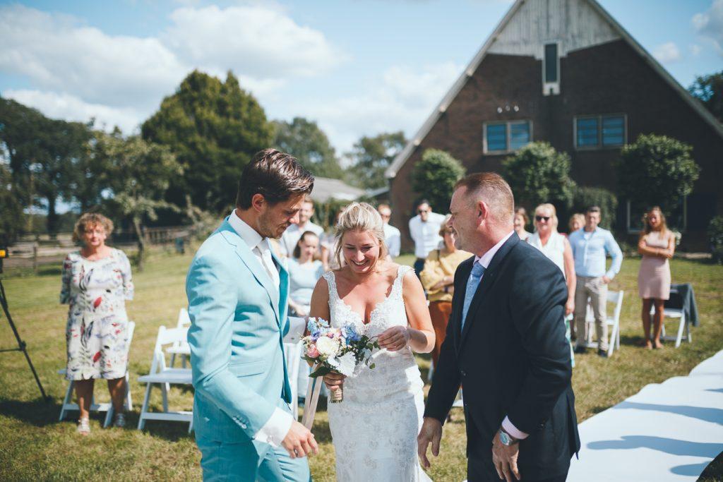Bruid komt aan bij bruidegom en plukt aan boeket tijdens bruiloft thuis op erf van oude boerderij trouwfotograaf Apeldoorn