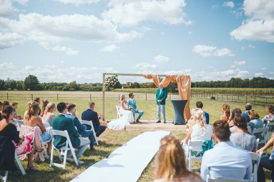 Bruid en bruidegom zitten onder altaar midden in het weiland in hun achtertuin met hun gasten op witte stoelen tijdens bruiloft thuis op erf van oude boerderij trouwfotograaf Apeldoorn