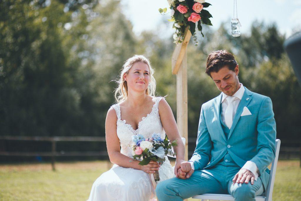 Bruid en bruidegom zitten naast elkaar en houden handen stevig vast tijdens bruiloft thuis op erf van oude boerderij trouwfotograaf Apeldoorn