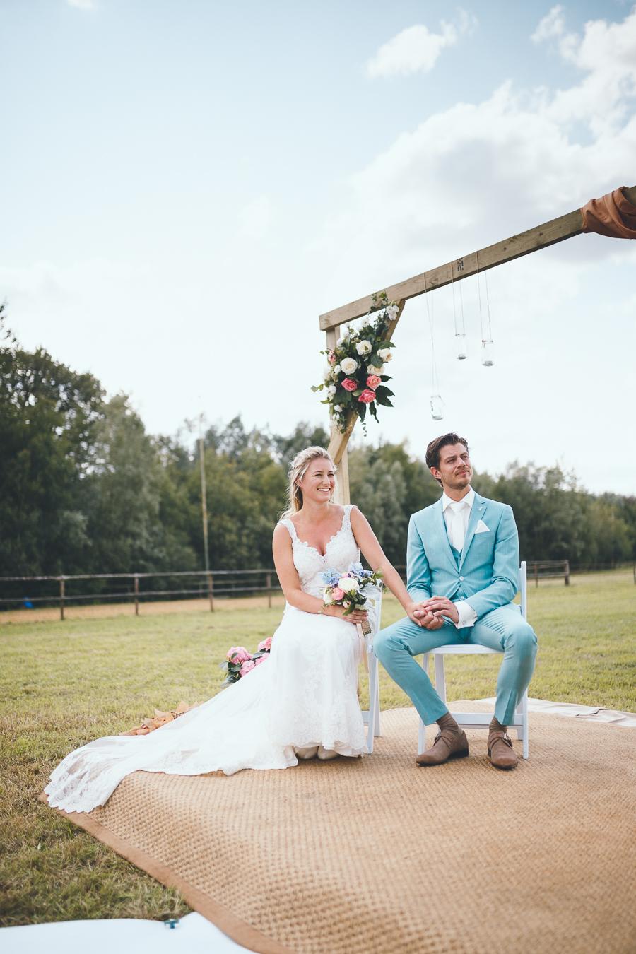 Bruid en bruidegom tijdens ceremonie onder altaar houden elkaar handen stevig vast en lachen naar trouwambtenaar tijdens bruiloft thuis op erf van oude boerderij trouwfotograaf Apeldoorn