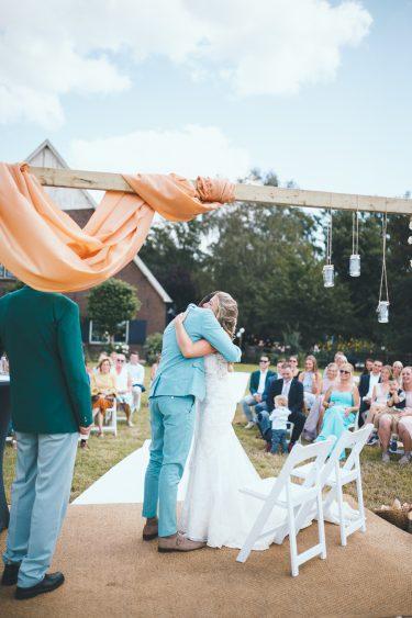 Bruid en bruidegom omhelzen elkaar tijdens ceremonie onder altaar met gasten op de achtergrond tijdens bruiloft thuis op erf van oude boerderij trouwfotograaf Apeldoorn