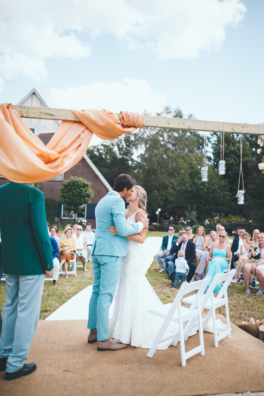 Bruid en bruidegom kussen elkaar onder het altaar tijdens ceremonie in hun achtertuin in het weiland tijdens bruiloft thuis op erf van oude boerderij trouwfotograaf Apeldoorn