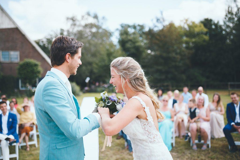 Bruid en bruidegom doen bij elkaar de ringen om en lachen tijdens bruiloft thuis op erf van oude boerderij trouwfotograaf Apeldoorn