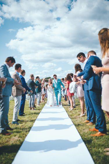Bruid en bruidegom lopen door erehaag van gasten heen over witte loper tijdens bruiloft thuis op erf van oude boerderij trouwfotograaf Apeldoorn